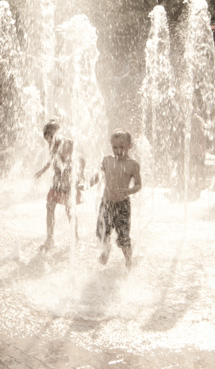 children run through fountain